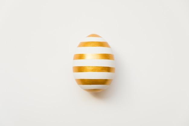 Uovo dorato di pasqua con motivo a strisce isolato su sfondo bianco. pasqua minima