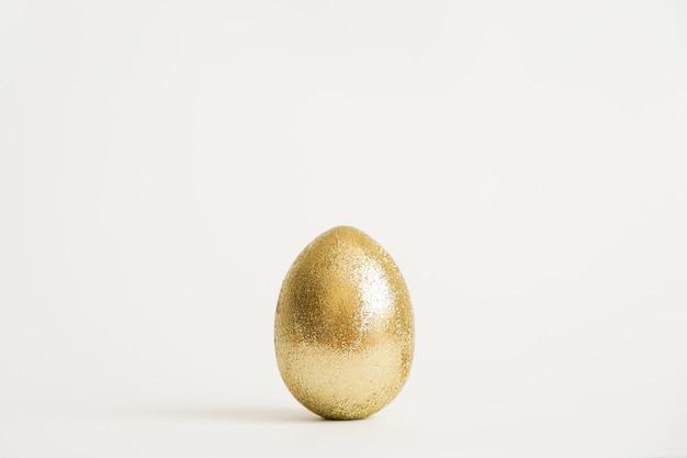 Uovo dorato di scintillio di pasqua isolato su priorità bassa bianca