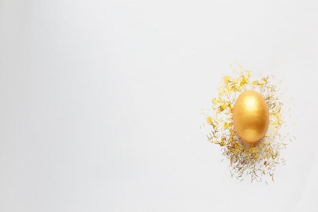 Uovo dorato e scintillii dorati su fondo bianco