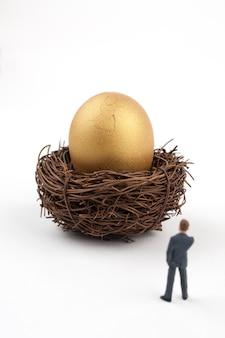 Uovo dorato incrinato e uomo d'affari