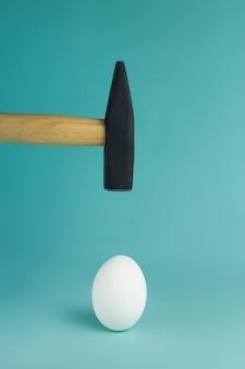 Uovo e martello aleggiano sopra di esso, prima del colpo.