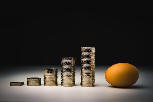 Uovo e molti soldi con pile di monete del grafico di inflazione