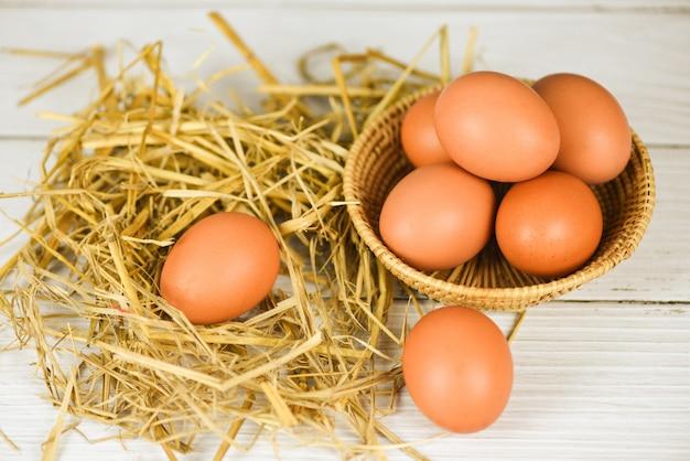 Uovo fresco sul canestro e paglia con la vista superiore del fondo di legno della tavola