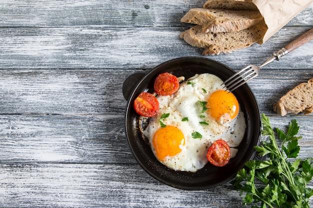 Uovo fritto. chiuda sulla vista dell'uovo fritto su una padella con pomodorini e prezzemolo