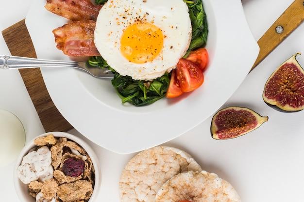Uovo fritto con fichi; cracker e cornflakes del soffio di riso su fondo bianco