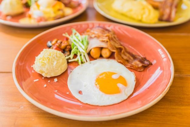 Uovo fritto con la patata di verdure del prosciutto della salsiccia di bacaon in piatto