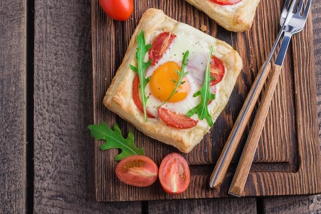 Uovo fritto della prima colazione sana con la ciliegia del pomodoro e del peperone sul bordo di legno