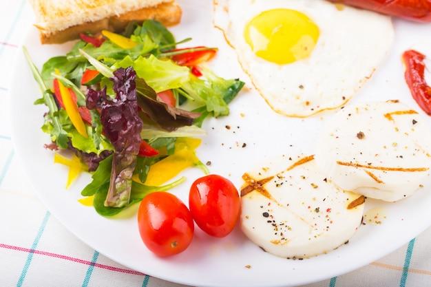 Uovo fritto e salsiccia sul piatto con insalata verde e formaggio