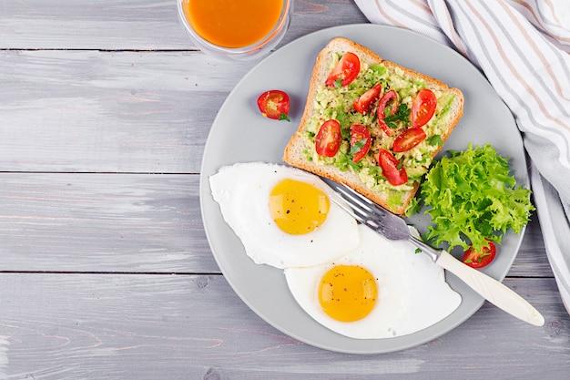 Uovo fritto, insalata di verdure e un panino alla griglia con avocado