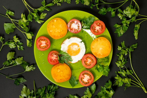 Uovo fritto laico piatto con pomodori colorati su sfondo chiaro