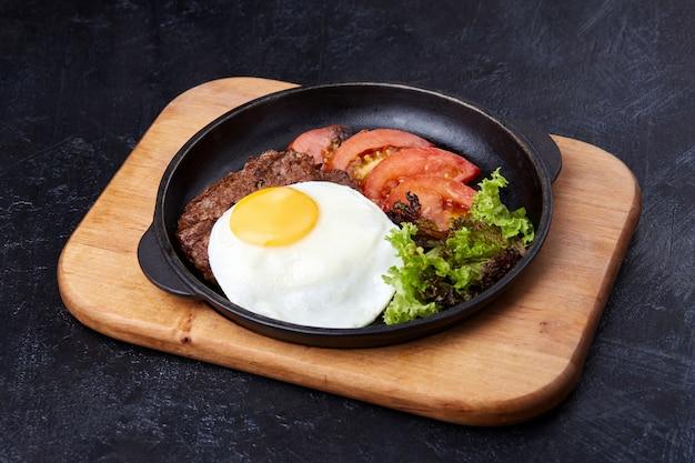 Uovo fritto padella, pomodori a fette, insalata e cotoletta