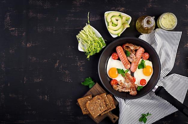 Uovo fritto, pomodori, salsiccia e pancetta