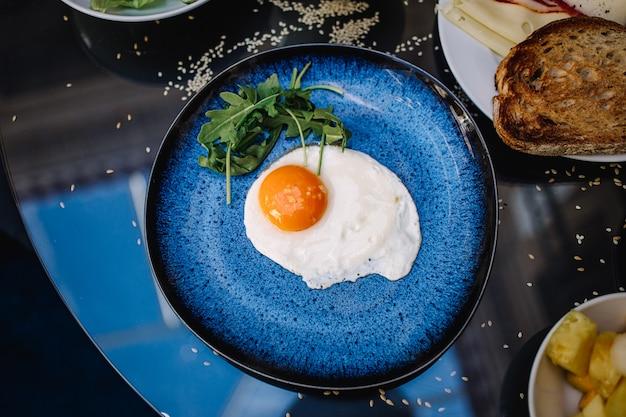 Uovo fritto su un piatto blu