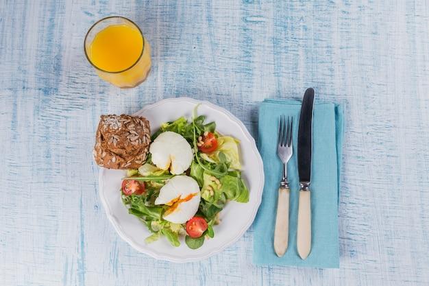 Uovo in camicia con insalata verde, pomodori, pane integrale e succo d'arancia su legno blu.