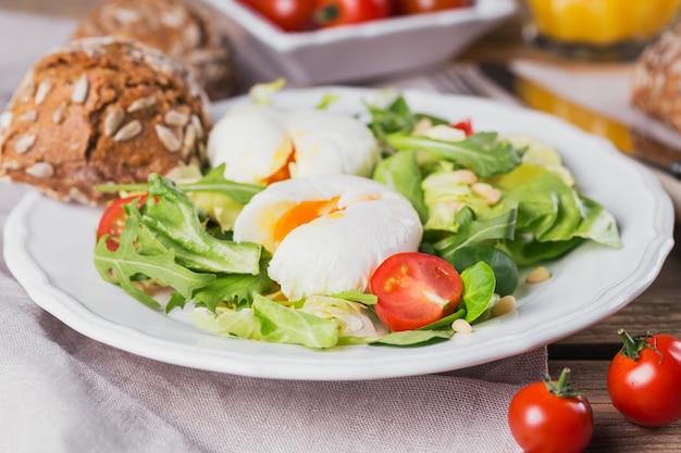 Uovo in camicia con insalata verde, pomodori, pane integrale e succo d'arancia su legno.