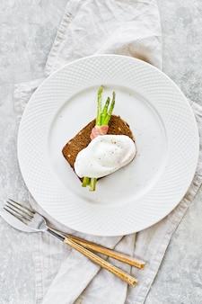 Uovo in camicia su mini asparagi alla griglia in pancetta.