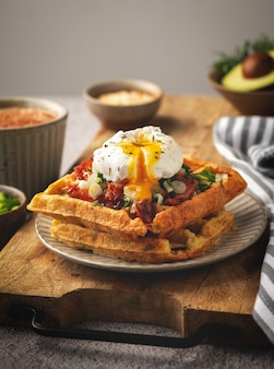 Uovo in camicia su waffle belgi, caffè, colazione