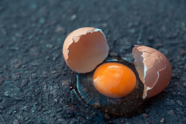 Uovo rotto su asfalto come simbolo di fallimento, esperienza negativa, distruzione, morte.