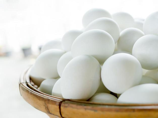 Uovo salato dell'anatra in canestro di bambù sulla vecchia tavola di legno in cucina