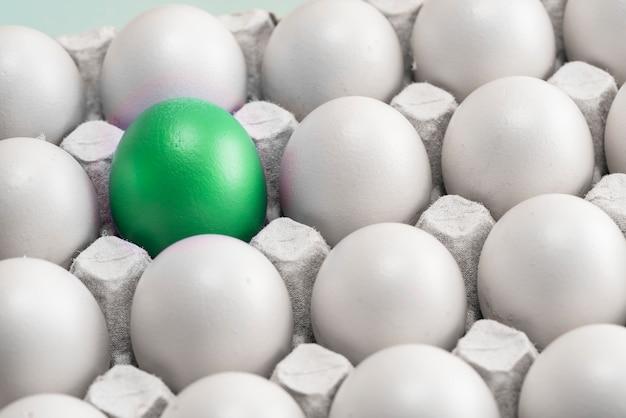 Uovo verde tra molte uova bianche nella scatola, primo piano. upstart e leader, simbolo di individualità.