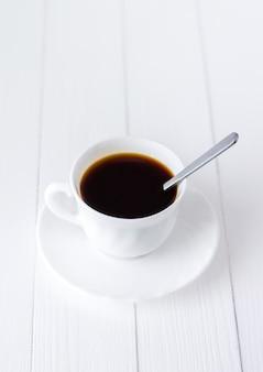 ? up del caffè del mattino su un fondo di legno bianco