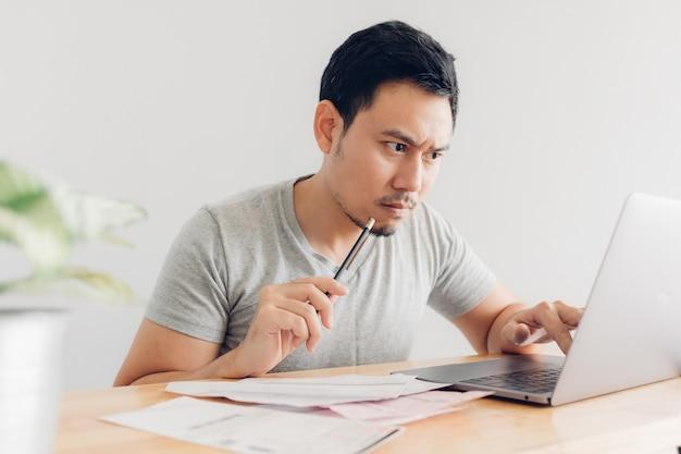 Upset e uomo serio ha problemi con fatturazione e debiti.