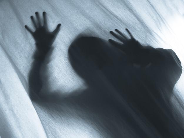 Urlando umano premendo attraverso la tenda del tessuto come sfondo horror