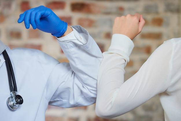 Urto del gomito. un nuovo modo di salutare per evitare la diffusione del coronavirus (covid-19). un dottore e una femmina si piegano sui gomiti invece di salutare con un abbraccio o una stretta di mano contro un muro di mattoni.