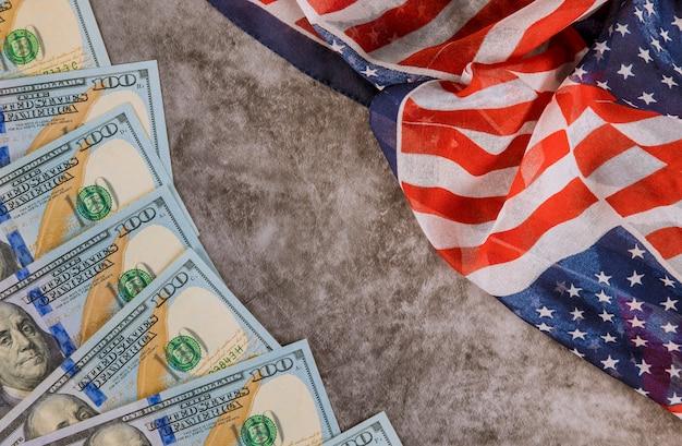 Us 100 dollari economici avvolti nella bandiera degli stati uniti