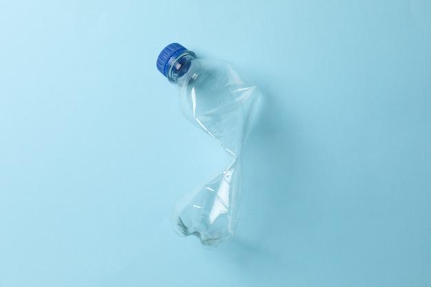 Usato bottiglia di plastica su blu, spazio per il testo