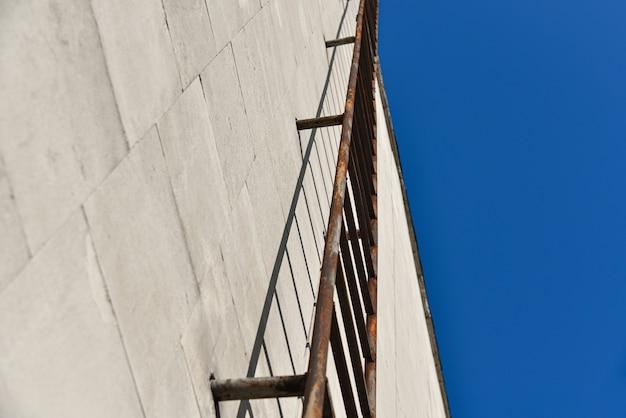 Uscita d'emergenza arrugginita su una parete della costruzione