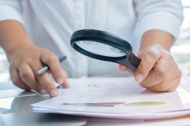 Uso asiatico dell'uomo d'affari i documenti di scansione della lente d'ingrandimento per il controllo investigano