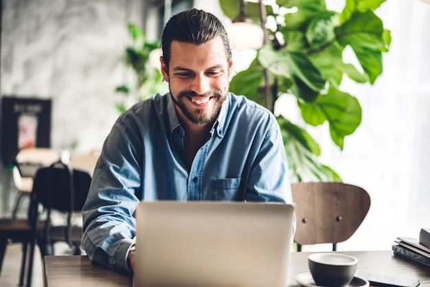 Uso barbuto bello dell'uomo dei pantaloni a vita bassa ed esaminare computer portatile con caffè alla tavola in caffè concetto di tecnologia e di comunicazione