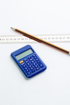 Uso blu della mano di contabilità del calcolatore con la matita della grafite e il righello trasparente sulla parete bianca