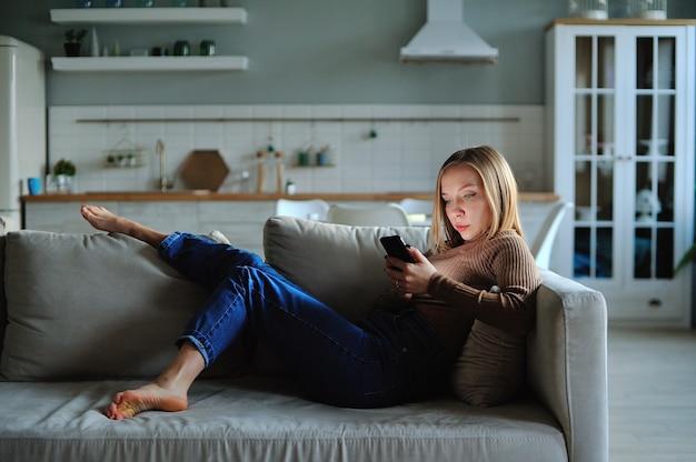 Uso della donna dello smartphone la sera a casa mentre si posa sul divano