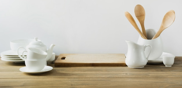 Utensili da cucina bianchi, stoviglie e altre cose bianche diverse per servire sul bordo di legno bianco.