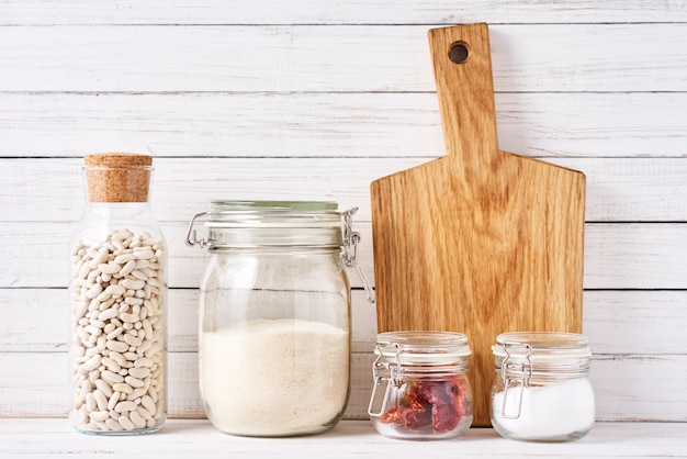 Utensili da cucina con tagliere e contenitori in vetro riutilizzabili con ingredienti alimentari. concetto di rifiuti zero