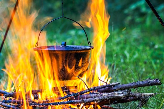Utensili da cucina da campeggio - pentola sul fuoco in un campeggio all'aperto con fiamme arancioni