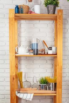 Utensili da cucina e stoviglie sulla mensola in legno