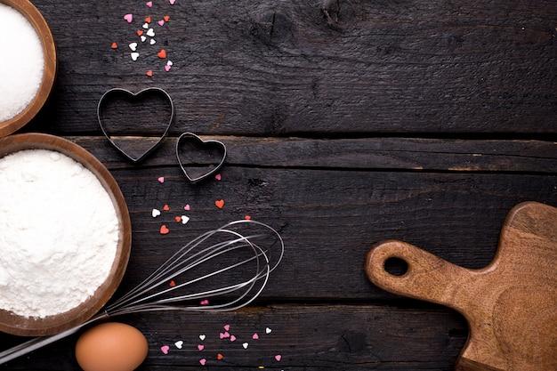 Utensili da cucina, farina e zucchero su legno