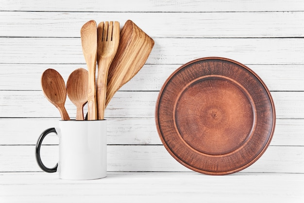 Utensili da cucina in tazza e piatto marrone su bianco