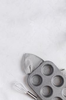 Utensili da cucina per la cottura - stampo in metallo per cupcake sbattere sul tovagliolo a righe spiegazzato.