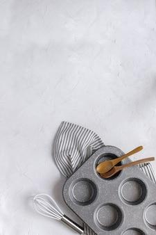 Utensili da cucina per la cottura - stampo per cupcake in metallo, frusta, cucchiai di legno su tovagliolo a righe spiegazzato.