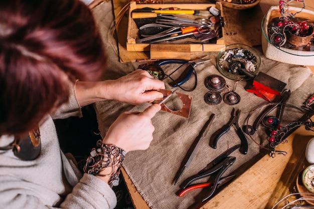 Utensili da lavoro fatti a mano con filo di rame sul tavolo con accessori. concetto di arte della gente dell'artigianato
