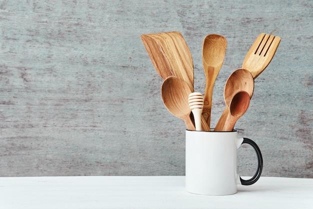 Utensili della cucina in tazza di ceramica su una priorità bassa grigia, spazio della copia