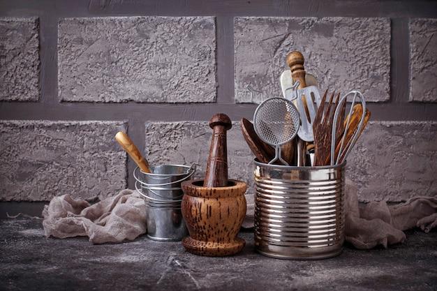 Utensili della cucina sulla priorità bassa del muro di mattoni. messa a fuoco selettiva
