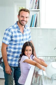 Utensili di lavaggio della figlia mentre padre che sta accanto a lei