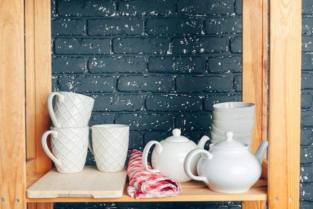 Utensili e tazze, utensili da cucina su ripiani in legno