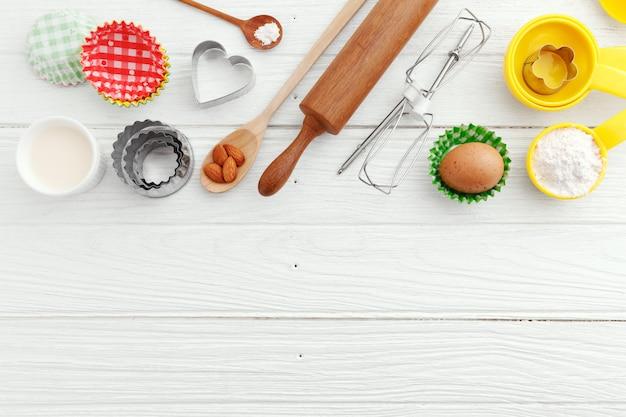 Utensili ed ingredienti di cottura su fondo di legno bianco