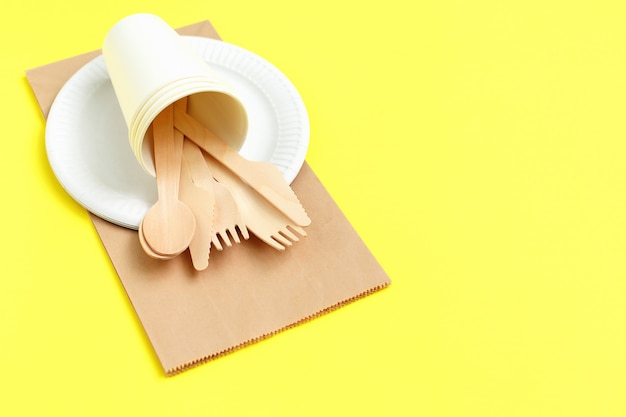 Utensili eliminabili ecologici fatti di legno di bambù sul sacco di carta su giallo